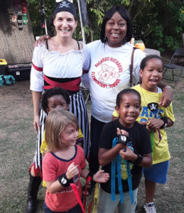 DoDat Founder Nora James poses with children and Principal Avion Matthew-James from Ricardo Richards School. (Source photo by Darshania Domingo)