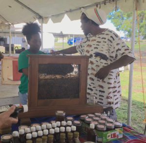 Beekeeper Roniel Allembert talks about bees in his observation hive. (Source photo by Susan Ellis)