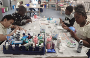 Students at Arthur Richards School paint holiday ornaments. Front table from left: Christian Diaz, 11, Rajun Charles, 11, Jesse Quilden, 10, and Tinye Isaac, 11. Back table: Caden Guirty, 10, Tahjai Young, 9, Cayla Diaz, 9. (Source photo by Susan Ellis)