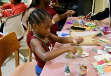 Amya Tyson chooses brightly colored spangles to decorate her Christmas ornament. (Source photo by Linda Morland)