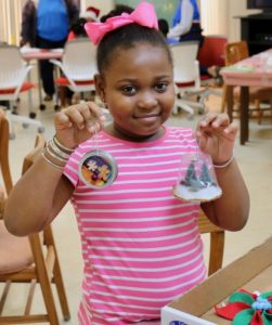 Jordin Jackson holds her two favorite Christmas ornaments from an afternoon of artistic fun. (Source photo by Linda Morland)