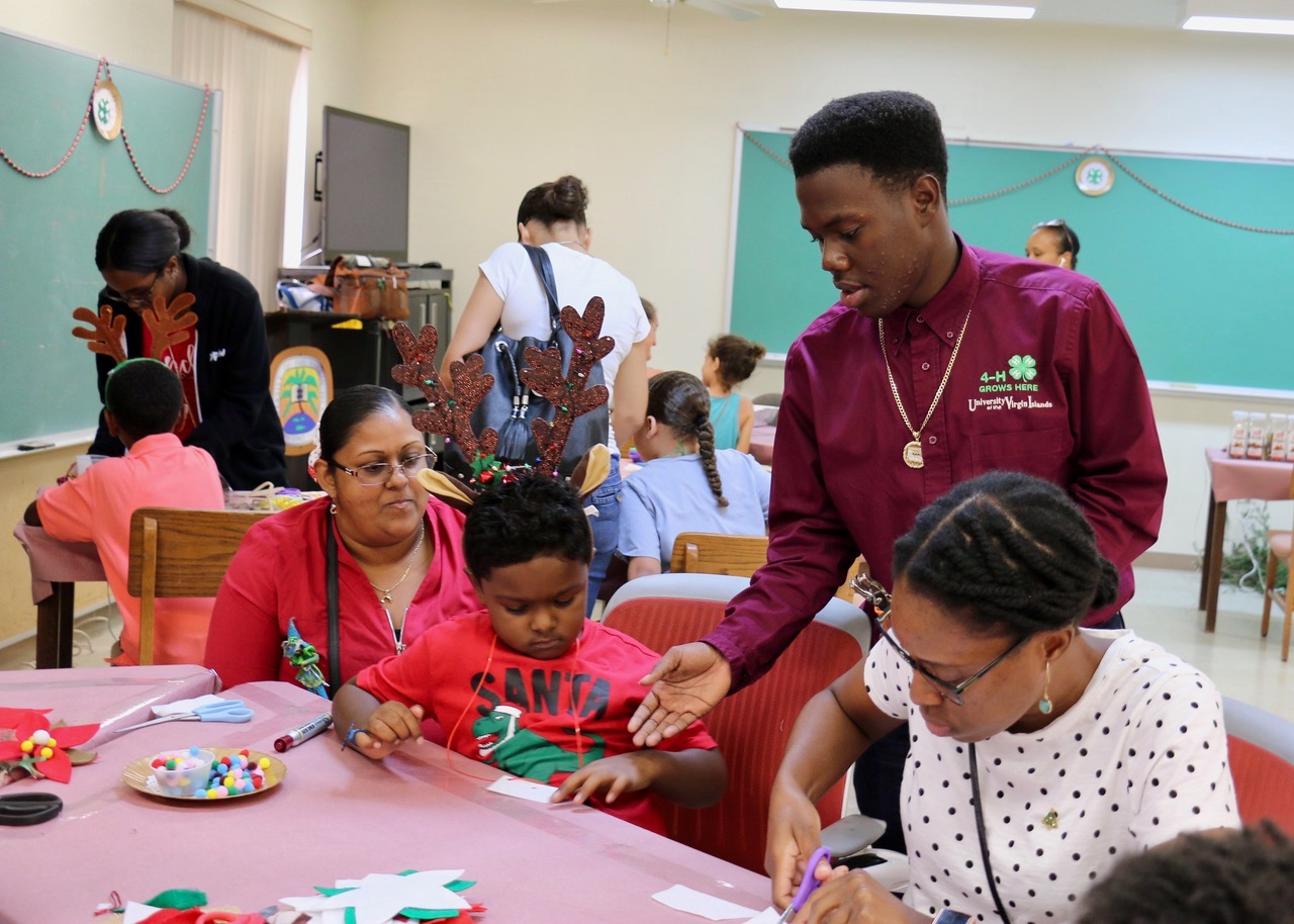 Trey Francis (standing) helps Sameer Parrilla as his mother, Jennifa Parrilla watches and Renisha Thomas works on an ornament. (Source photo by Linda Morland)