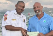Clarence Stephenson receives a $5,000 check from Dominick DeDominicis of Haugland Virgin Islands for an STJ children's Christmas party. (Photo by VIFS)