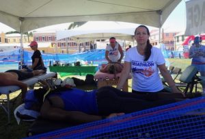 Vicki Hicks, front and Viktoria Reed massage triathletes after they finish the race. (Source photo by Susan Ellis)