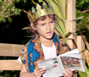 """As one of the Three Wise Men, Kaiden Castillo wears a golden crown during """"We Three Kings of Orient Are."""" (Source photo by Linda Morland)"""