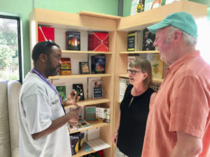 Magabe Calixte discusses products with Paula and Greg Hachmeister. (Source photo by Amy Roberts)