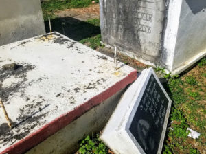 A fallen tombstone is wedged in between two graves sites making it difficult to pass. (Source photo by Bethaney Lee)