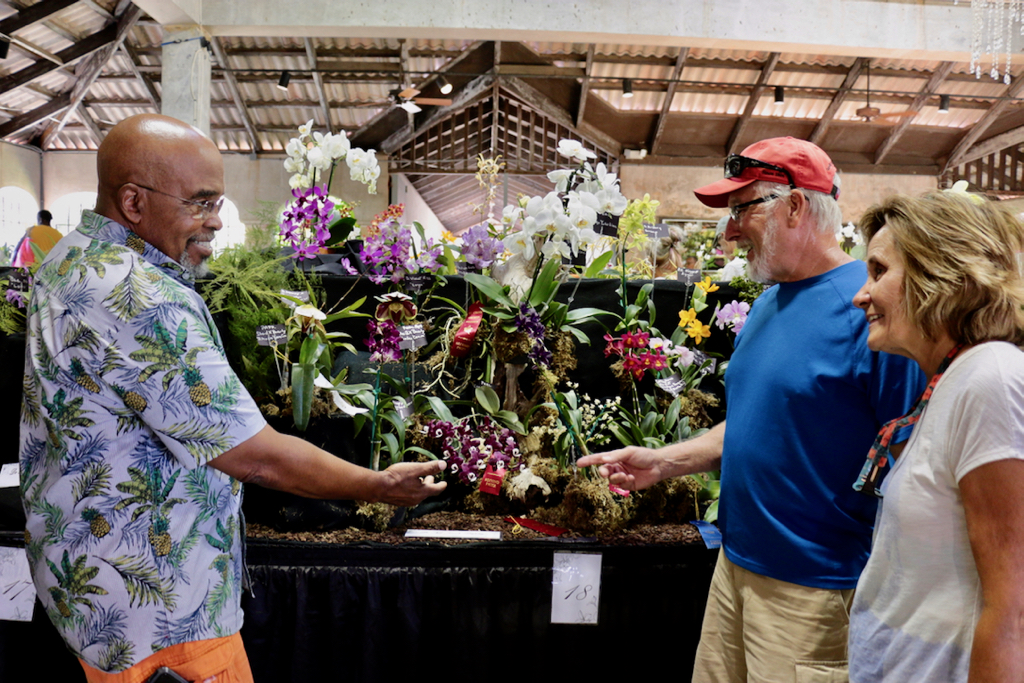 Luther Edwards of The St. Croix Orchid Society assists Paul and Denise Langevin of New Jersey with questions. (Source photo by Linda Morland)