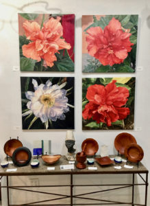 Karen's floral paintings hang above Avelino's carving at Bajo El Sol Gallery. (Source photo by Amy Roberts)