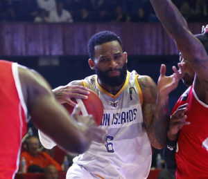 USVI point guard Walter Hodge battles past a pair of Cuban defenders in Friday's game in Havana. (Photo by FIBA)