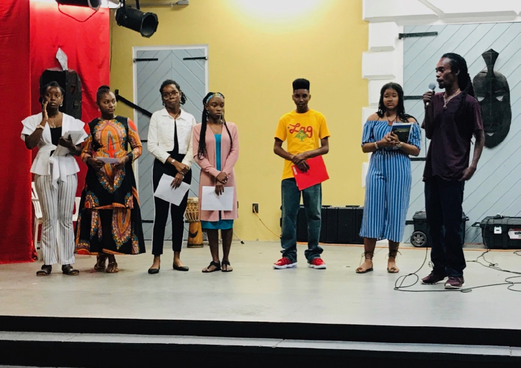 St. Croix Central High ninth graders, from left, Angelina Valentine, Elicia Wattley, Bry'nice Berley, Jedaya George, Anwar Mohammad, Quishylah Navaro, and their teacher Geron Richards read their own poetry drawn from their knowledge of their history and culture. (Source photo by Elisa McKay)