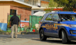 A police officer looks into a yard at the entrance to Hospital Ground. (Source photo by S. Pennington)