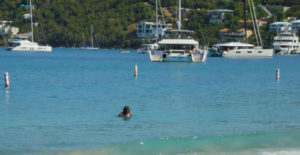 A local woman takes a sea bath in shadow of yachts Sunday. (Source photo by S. Pennington)
