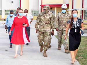 Health Commissioner Just a Encarnacion, in the red dress, Brig. Gen. Kodjo Knox-Limbacker, the adjutant general of the Virgin Islands National Guard, to her right, and other USVI officials tour the Alternate Care Facility. (Photo submitted by FEMA)