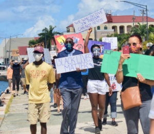 """During Saturday's protest march, UVI President David Hall attends the March and holds up a sign that reads """"Black Lives Matter."""" (Source photo by Kyle Murphy)"""