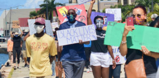 "During Saturday's protest march, UVI President David Hall attends the March and holds up a sign that reads ""Black Lives Matter."" (Source photo by Kyle Murphy)"