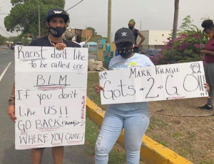Protestor spread their message in front of the WAPA office. (Source photo by Diana Dias)