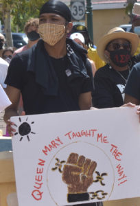 In Roosevelt Park, A protester holds up a sign referencing Queen Mary, one of the leaders of the Fireburn protest of 1878. (Source photo by Kyle Murphy)