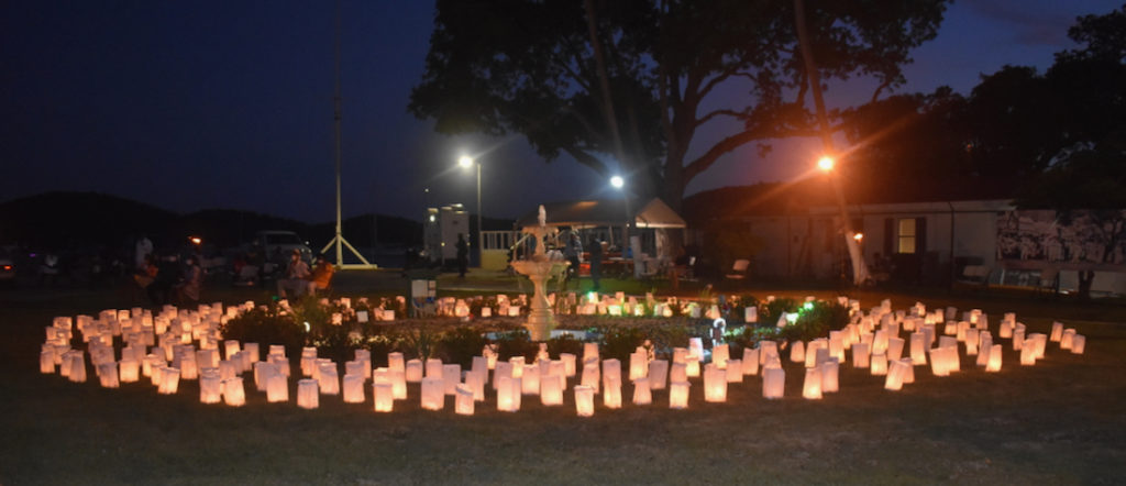 The luminaria – candles in a paper bag weighted with sand – shine on the lawn of Legislative building, memorializing some of those lost to gun violence. (Source photo by Kyle Murphy)