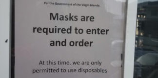 A sign in the window of a Virgin Islands eatery lays out the rules of the new normal . (Soure photo by Adian Brewer)